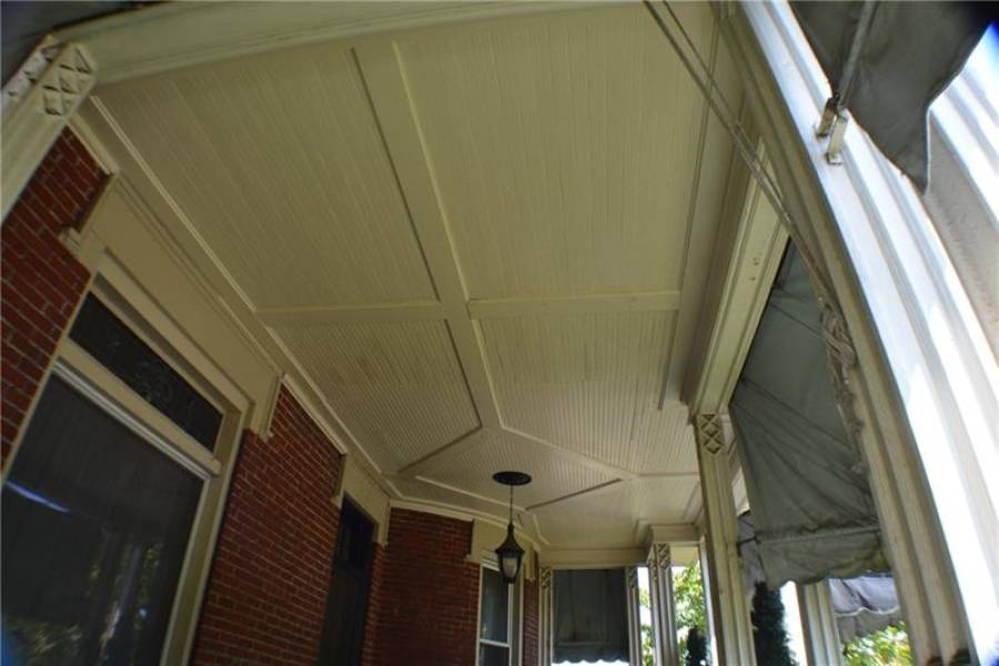 Large covered front porch with period details.