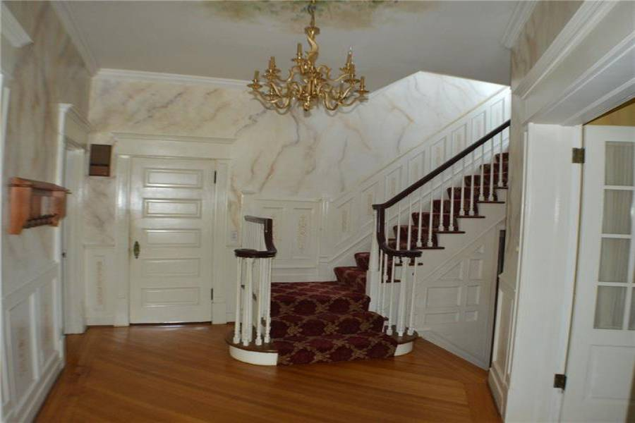 Grand foyer with lovely chandelier. Inlaid flooring.