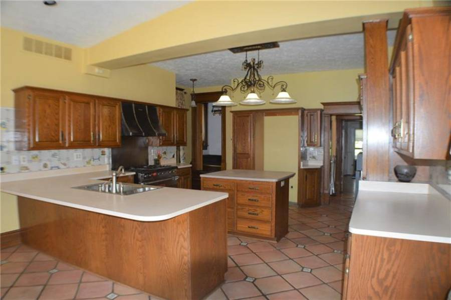 This kitchen has tons of cabinets, island, breakfast bar, and attached butler's pantry!